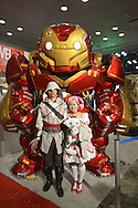 Manhattan, New York City, New York, USA. October 10, 2015. In front of large Iron Man statue pose boy and girl cosplayers portraying (L-R) Ezio a member of Italian House of Auditore from Assassin's Creed and pink hair schoolgirl Magi Madoka Kaname from Puella Magi Madoka Magica anime, at the 10th Annual New York Comic Con. NYCC 2015 is expected to be the biggest one ever, with over 160,000 attending during the 4 day ReedPOP event, from October 8 through Oct 11, at Javits Center in Manhattan