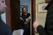 Standing in his apartment doorway, Rudolph Nixon, a Springfield, MA, resident talks with Bernie Sanders volunteers canvasing the area, Monday, Feb. 29, 2016.  CREDIT: Cheryl Senter for The New York Times