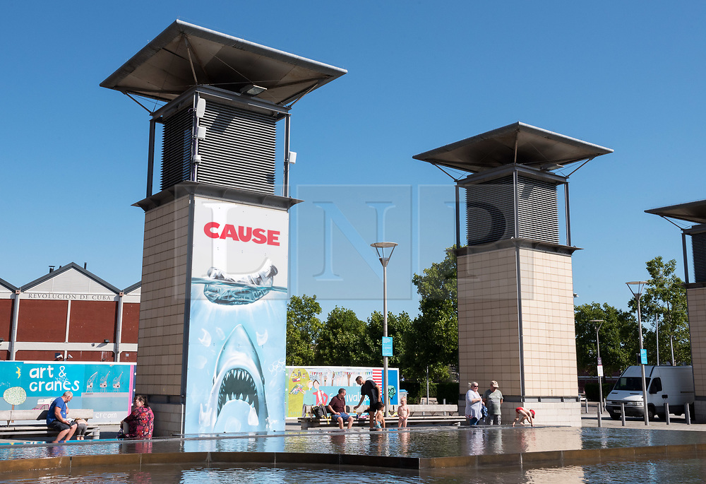 """© Licensed to London News Pictures. 23/08/2019. Bristol, UK. Mural titled """"Cause"""" by Bristol artist Jody Thomas which references the instantly recognisable poster from the film """"Jaws"""" and aims to highlight the impact of single-use plastic pollution on the Earth's oceans. The piece is painted on a ventilation tower for the underground carpark in Bristol's Millennium Square in collaboration with We The Curious science and arts centre in Bristol's Millennium Square. We The Curious declared their own climate emergency earlier this year, becoming the first science centre in the world to do so. The science centre formed a partnership with Bristol City Council and the University of Bristol, who collectively released a public declaration to become carbon neutral by 2030. Jody who began painting in 1988 also painted the giant mural of Greta Thunberg on Bedminster's Tobacco Factory earlier this yearPhoto credit: Simon Chapman/LNP."""