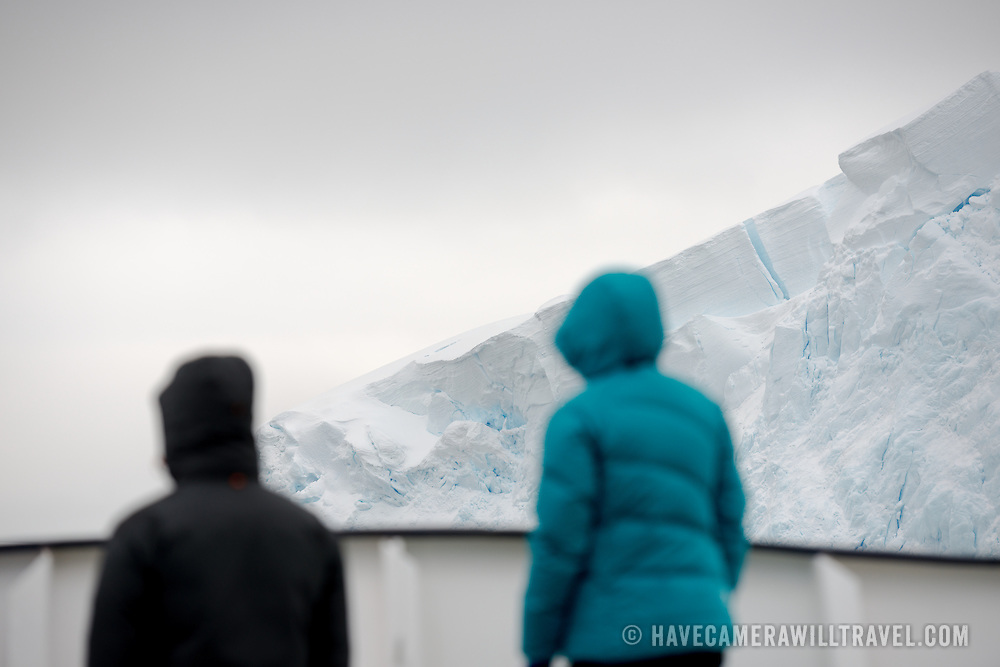 """Two passengers stand on the deck of a ship passing through the beautiful Lemaire Channel on the western side of the Antarctic Peninsula. The Lemaire Channel is sometimes referred to as """"Kodak Gap"""" in a nod to its famously scenic views."""
