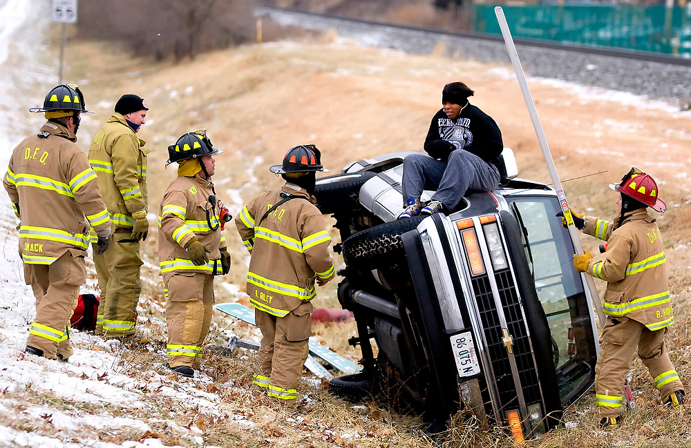 Decatur firefighters help a motorist down from their pickup truck after the vehicle slid off the road and rolled over in the ditch along westbound U.S. Highway 36 just north of Fairview Park Tuesday, Dec. 23, 2008, in Decatur, Ill.