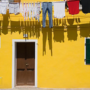 Clean laundry hangs out to dry on clothesline above doorway and shuttered windows of bright yellow painted house in Burano, Italy