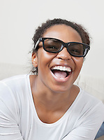 Cheerful young African American woman wearing 3D glasses and watching TV