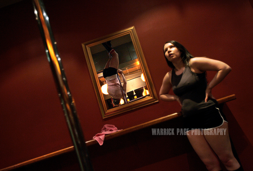 "MELBOURNE, AUSTRALIA - AUGUST 7: High-school teacher Johanna Dutton (R), 26, watches instructor Andi (L), 33, perform a complicated move during an advance pole dancing class at the Imperial Hotel, August 7, 2006, Melbourne, Australia. Previously reserved for strip clubs, pole dancing is now quickly becoming a new fitness crazy throughout Australia, Europe and the US with thousands of women from all walks of life leaving traditional gymnasiums for the more social and challenging art of pole dancing. Pole dancing for fitness exploded onto the public scene after celebrities such as Angelina Jolie, Jennifer Anniston and Britney Spears professed it was their favourite form of exercise. Classes are often small in numbers giving a more personal atmosphere and strong bonds of friendship are often formed between students and instructors. Instructors claim a noticeable increase in their students' self-confidence after only a few weeks. Most students claim even thought it's a rigorous workout, they're having so much fun it doesn't feel like exercise at all. According to ""Polestars"", a British company that began setting up classes throughout six Australian cities in 2004,  ""a good session on the pole"" can burn more calories than at the gym and provide more muscle tone. (Photo by Warrick Page)"