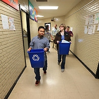 Tony Mays, left, and Kaylee Maddox carries indivual recycling bins to combine as they make their way around Tupelo Middle School and collect all the schools recycleables.
