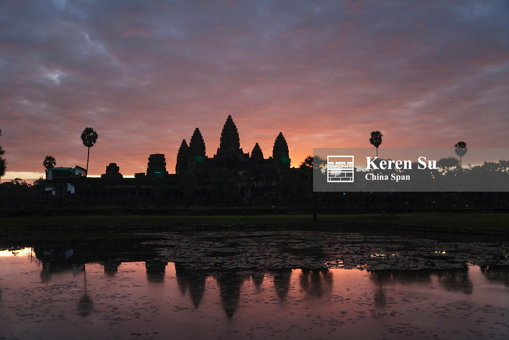 Towers of Angkor Wat and reflection in the river at sunrise, UNESCO World Heritage site.