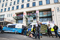 London, UK. 15th April 2019. Two climate campaigners from Extinction Rebellion continue to occupy an area above the main door to the Shell Centre during 'International Rebellion UK - Shut Down London!' in protest against the company's involvement in ecocide. Three fellow campaigners were earlier arrested after daubing graffiti on the exterior of the building, smashing a revolving door and glueing themselves to the door. Credit: Mark Kerrison/Alamy Live News