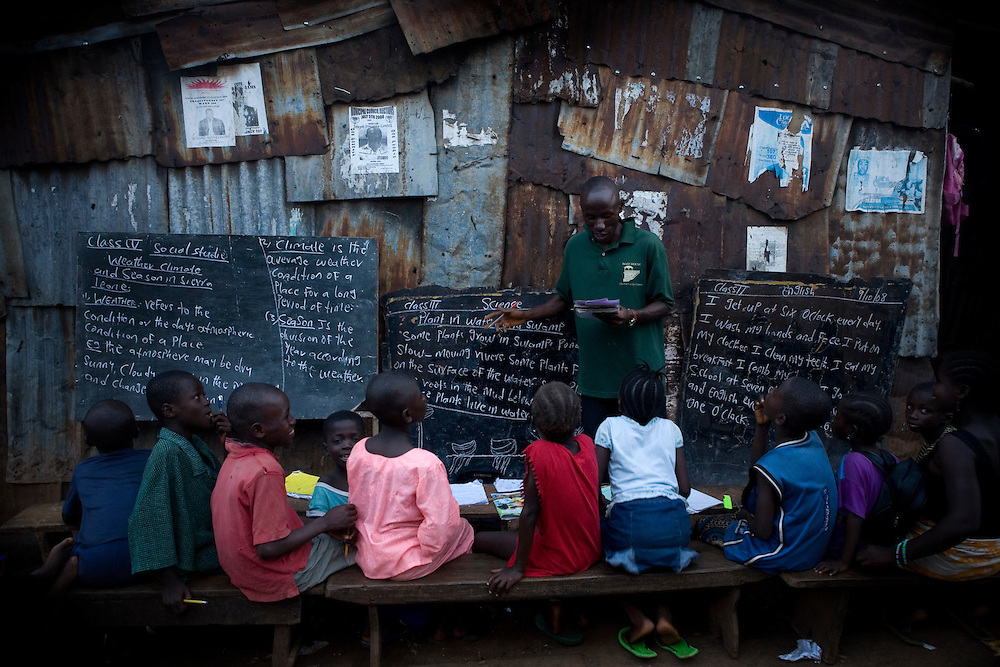 A class is taught in a narrow passage in Kroo Bay slum every evening, the teacher is funded by an NGO. Kroo Bay, Freetown, Sierra Leone.