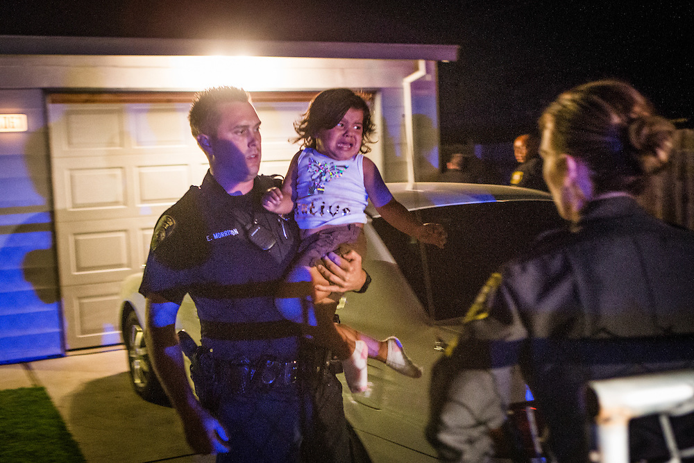 Stockton Police officer Eric Morrison carries a child out of a home while searching for a gang member as part of the Community Response Team which targets violent gangs in Stockton, California, September 18, 2013. Facing stark and rising homicide rates, the California cities Oakland and Stockton are taking a second chance at a novel method of disrupting street gangs, called Ceasefire, in which the police use social-analytics software to map out connections between a city's most violent gang members, using the data to make targeted and coordinated arrests.