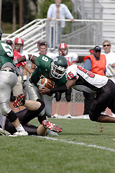 09 September 2006 Titan Running Back Marcus Dunlop tries to escape the Comets defense..In the first ever football competition between the Olivet Comets and the Illinois Wesleyan Titans, the Titans strut off the field with a 21- 6 victory. .Game action took place at Wilder Field on the campus of Illinois Wesleyan University in Bloomington Illinois.