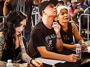 28 OCTOBER 2018 - BANGKOK, THAILAND: Judges score a man's tattooed arm during judging of the Realistic division at the 2018 MBK Center Tattoo Fest. Tatoo artists from around the world came to participate in the festival, which featured both modern (using tattoo machines) and traditional methods (done by hand with long needles) of tattooing.     PHOTO BY JACK KURTZ