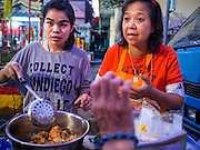 18 JANUARY 2015 - BANGKOK, THAILAND:  Food vendors sell Thai deep fried snacks during a Sai Yong Hong Opera Troupe performance at the Chaomae Thapthim Shrine, a Chinese shrine in a working class neighborhood of Bangkok near the Chulalongkorn University campus. The troupe's nine night performance at the shrine is an annual tradition and is the start of the Lunar New Year celebrations in the neighborhood. The performance is the shrine's way of thanking the Gods for making the year that is ending a successful one. Lunar New Year, also called Chinese New Year, is officially February 19 this year. Teochew opera is a form of Chinese opera that is popular in Thailand and Malaysia.             PHOTO BY JACK KURTZ