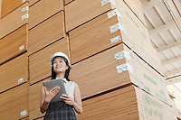 Low angle view of female industrial worker holding tablet PC with stacked wooden planks in background