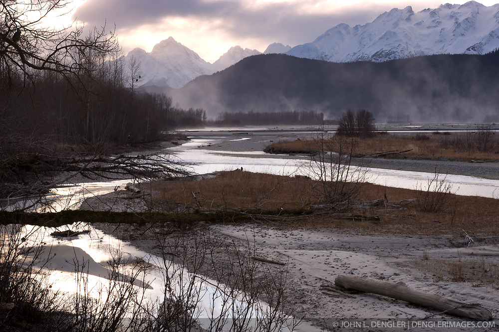What appears to be fog rising off the Chilkat River gravel bar is actually blowing dust caused by high winds sweeping through the Chilkat River valley in the Alaska Chilkat Bald Eagle Preserve near Haines, Alaska