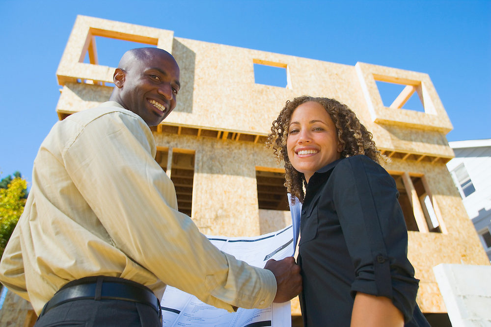 Portrait of smiling young couple with new home under construction.