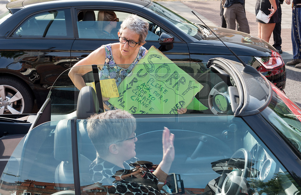 "© Licensed to London News Pictures. 17/07/2019; Bristol, UK. Extinction Rebellion Summer Uprising 2019. A ""De-escalation"" member speaks to motorists stuck in traffic blocked by Extinction Rebellion to explain the reasons for the action. Extinction Rebellion block a major road junction at morning rush hour on Newfoundland Road coming into Bristol city centre causing traffic delays up the M32 to the M4 motorway. Campaigners locked themselves onto a pink bath tub, and held 7 minute roadblocks on other parts of the junction complex. Extinction Rebellion are holding a five-day 'occupation' of Bristol, by occupying Bristol Bridge in the city centre and traffic has to be diverted and carrying out other events. As part of a country-wide rebellion called Summer Uprising, followers will be holding protests in five cities across the UK including Bristol on the theme of water and rising sea levels, which is the group's focus for the South West. The campaign wants the Government to change its recently-set target for zero carbon emissions from 2050 to 2025. Photo credit: Simon Chapman/LNP."