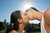 Couple kissing in park in bright sunlight
