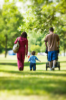 Young couple walking with child in the park.