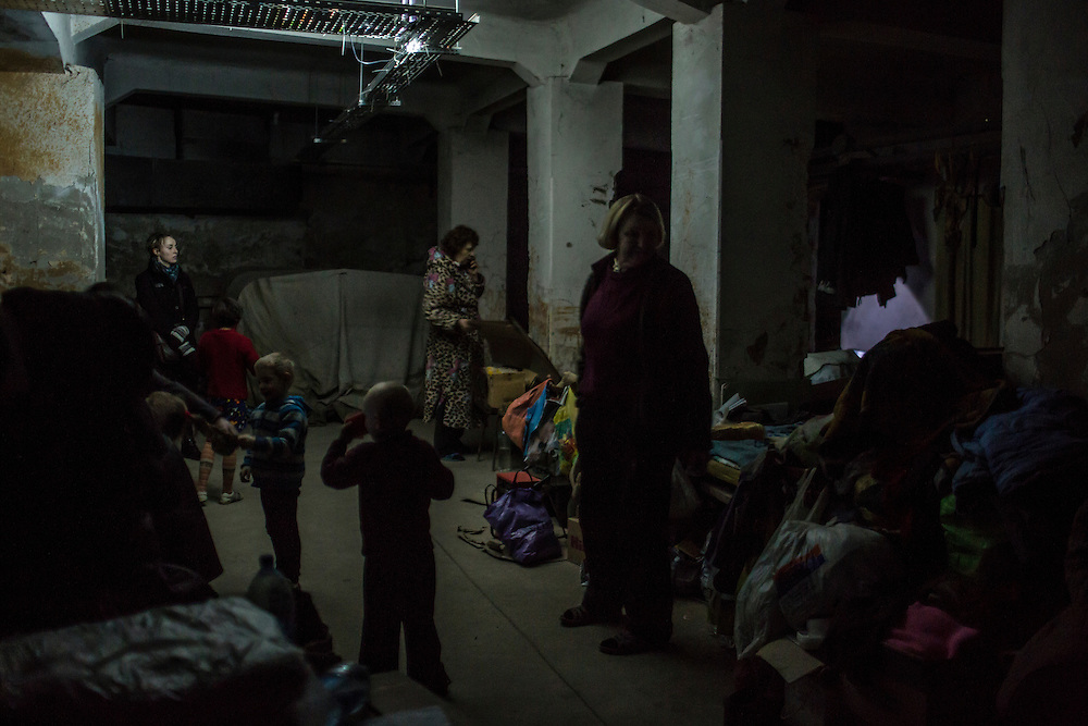 DONETSK, UKRAINE - JANUARY 29, 2015: Local residents are illuminated by a single dim bulb during a power outage in an underground bomb shelter in the Petrovskyi district of Donetsk, Ukraine. The neighborhood has been shelled heavily in the past few days, forcing many people back to the shelters they first fled to in the summer. CREDIT: Brendan Hoffman for The New York Times
