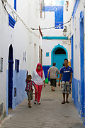 Street architecture and local life, Asilah, Northern Morocco, 2015-08-10.<br /><br />Asilah is a sleepy fishing town in the North of Morocco, just one hour south of Tangier. While not completely off Morocco's well-beaten path, it's often missed by travellers bound inland for Fez or Chefchaouen, yet has a uniquely alluring charm. With an immaculately restored medina that's re-painted vivid shades of blue & white each summer, Asilah has the feel of being Morocco's own Santorini - a great spot to see the more chilled out, seaside town life in Morocco.  <br /><br />The town lies in the middle of a fascinating history in historical, architectural and artistic terms. It's 3,600 year old history that includes a varied range of occupiers, involving Roman, Arab Portuguese, Spanish and French colonisation. Many famous writers and artists have spent time here; in ancient times is it reported Herecules did a tour of the area and, more recently; Paul Bowles, Tennessee Williams, Edith Wharton, Jean Genet (who is buried in the nearby town of Larache), William Burroughs, Jimi Hendrix and Henri Matisse have all found the area inspiring. The Portuguese ramparts remain fully intact and a full day can be spent wandering through its old gates and the ever narrowing medina streets inside the walls.<br /><br />The architecture in Asilah has been heavily influenced by these different periods of occupation, which is one of the main reasons for its unique and characterful feel. Evidence of Mediterranean design can be seen in the rampart walls and gates themselves, reflecting the Spanish & Portuguese influence on the Asilah's development, Roman ruins can be found in the nearby town of Larache and Arab influences are more subtly found in the decorative window shutters and the labyrinth like medina layout to the streets. <br /><br />If a lover of the quirkier details found in the medinas of Morocco, then Asilah won't disappoint, with hundreds of creatively designed doorways, decorative window s