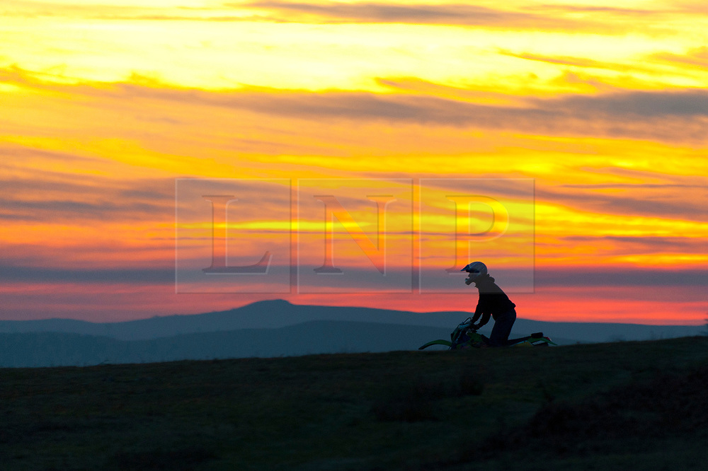 © Licensed to London News Pictures. 24/02/2019. Brecon, Powys, Wales, UK. A motocross biker is sihouetted against the sky after a beautiful spring-like day as the sun sets over moorland near Brecon in Powys, Wales, UK. Photo credit: Graham M. Lawrence/LNP