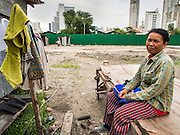 04 SEPTEMBER 2013 - BANGKOK, THAILAND:  A Cambodian woman waits for her laundry to dry on the construction site of a new high rise apartment / condominium building on Soi 22 Sukhumvit Rd in Bangkok. The woman lives in the corrugated metal dorms that serve as worker housing. Most of the workers at the site are Cambodian immigrants.    PHOTO BY JACK KURTZ