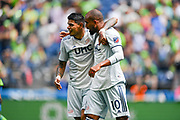 Teal Bunbury #10 and Gustavo Bou #7 of New England Revolution celebrate after a goal against the Seattle Sounders a MLS soccer match on Saturday, Aug. 10, 2019, in Seattle. The teams played tp a 3-3 tie. (Alika Jenner/Image of Sport)