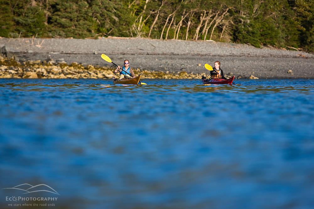 A man and woman sea kayaking near Burnt Porcupine Island in Maine's Acadia National Park.  Bar Harbor.