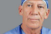 Close-up of senior male doctor over gray background