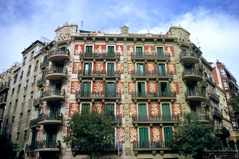 An ornate apartment building stands proudly on a city street in Barcelona, Spain.