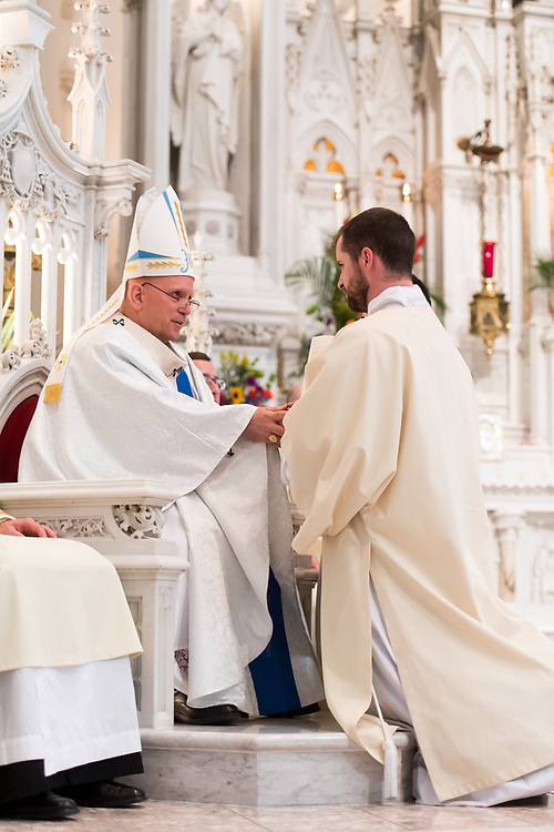 DENVER, CO - MAY 13: Denver Archbishop Samuel Aquila holds Daniel Eusterman's hands for the promise of respect and obedience for his ordination of the priesthood at the Cathedral Basilica of the Immaculate Conception on May 13, 2017, in Denver, Colorado. (Photo by Daniel Petty/for Denver Catholic)