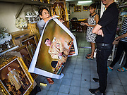 01 DECEMBER 2016 - BANGKOK, THAILAND:  A shopkeeper rolls up a portrait of Crown Prince Vajiralongkorn, who will soon be the new King of Thailand. Thailand's parliamentary body, the National Legislative Assembly, invited HRH Crown Prince Maha Vajiralongkorn to be king following the death of the Crown Prince's father, Bhumibol Adulyadej, the Late King of Thailand. The invitation marked the formal beginning of the process of naming the new King, although Crown Prince Vajiralongkorn was the heir apparent and Bhumibol's appointed successor. Shops that sell royal paraphernalia are now selling new portraits of  Crown Prince Vajiralongkorn which will be displayed alongside portraits of his late father. King Bhumipol died on Oct 13.     PHOTO BY JACK KURTZ