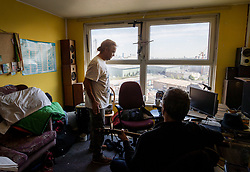 © Licensed to London News Pictures. 11/08/2017. London, UK. Resident Tyrone Thomas (L) stands in his 9th floor flat after being given a cooking hotplate by the council after the gas was turned off. Residents on the Ledbury Estate in south London have been told they will have to leave their properties over the next few weeks. A structural survey carried out after the Grenfell fire found cracks that could lead to a collapse of the building if a gas explosion occured in one of the flats. Photo credit: Peter Macdiarmid/LNP