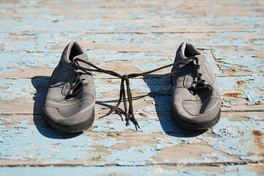 POZZALLO, ITALY - 27 JULY 2015: A pair of shoes belonging to a migrant is left on the wreck of a boat used by smugglers to cross the Mediterrannean Sea, here in the so-called boat cemetery of Pozzallo, Sicily, Italy, on July 27th 2015.