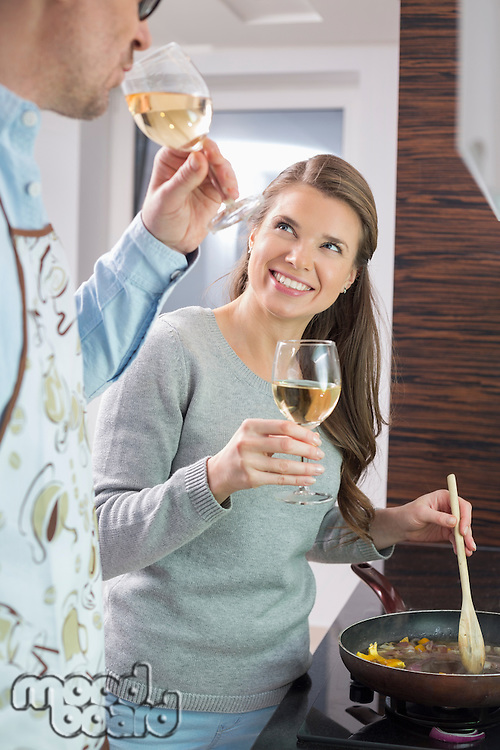 Happy woman having wine with man while cooking in kitchen