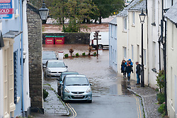 © Licensed to London News Pictures. 13/10/2018. Crickhowell, Powys, Wales, UK. Residents and locals check out the extensiveflooding at Crickhowell in Powys Wales, UK.  Fireservices pump out The Bridge End Inn, (landlord Howard Baker) at Crickhowell in Powys, Wales, UK.Storm Callum continues to devastate South Wales as the River Usk bursts it's banks as a result of  massive torrential rainfall in Powys flooding many riverside properties. Photo credit: Graham M. Lawrence/LNP