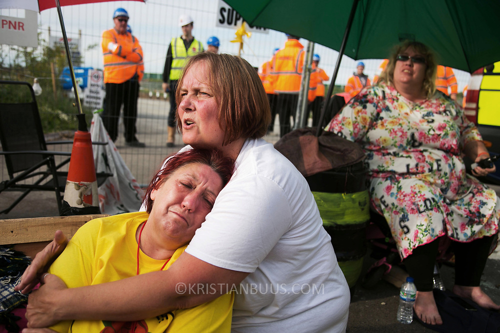 13 local activists locked themselves in specially made arm tubes to block the entrance to Quadrilla's drill site in New Preston Road, July 03 2017, Lancashire, United Kingdom. An exhausted Alana McCullogh has released herself from her armlock after 15 hours and is looked after by a friend.  The 13 activists included 3 councillors; Julie Brickles, Miranda Cox and Gina Dowding and Nick Danby, Martin Porter, Jeanette Porter,  Michelle Martin, Louise Robinson,<br /> Alana McCullough, Nick Sheldrick, Cath Robinson, Barbara Cookson, Dan Huxley-Blyth. The blockade is a repsonse to the emmidiate drilling for shale gas, fracking, by the fracking company Quadrilla. Lancashire voted against permitting fracking but was over ruled by the conservative central Government. All the activists have been active in the struggle against fracking for years but this is their first direct action of peacefull protesting. Fracking is a highly contested way of extracting gas, it is risky to extract and damaging to the environment and is banned in parts of Europe . Lancashire has in the past experienced earth quakes blamed on fracking.