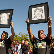 Visibly emotional, Pat Gibson, left, and Valerie Davis hold signs of two of the victims killed in the Parkland shooting during the one-month anniversary outside Marjory Stoneman Douglas. Nikolas Cruz is accused of using a semiautomatic AR-15 rifle to commit the murders. <br /> Photography by Jose More