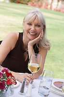 Mature elegant woman sitting at table outdoors