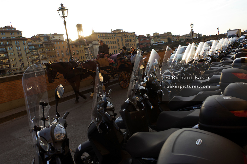 Tourists ride in a horse drawn carrage past scooters and bikes along river Arno north bank in city of Florence.