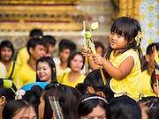 05 DECEMBER 2014 - BANGKOK, THAILAND: A girl on her father's shoulders carries lotus buds in the Grand Palace Friday morning before a service for Bhumibol Adulyadej, the King of Thailand. Thais marked the 87th birthday of the King Friday. The revered Monarch was scheduled to make a rare public appearance in the Grand Palace but cancelled at the last minute on the instructions of his doctors. He has been hospitalized in Siriraj Hospital, across the Chao Phraya River from the Palace, since early October.    PHOTO BY JACK KURTZ