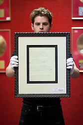 © Licensed to London News Pictures. 28/06/2013. London, UK. A Bonhams employee holds David Bowie's handwritten lyrics for his track 'The Jean Genie' (est. GB£12,000-15,000) in London today (28/06/2013) at the press view for an entertainments auction being held at Bonham's Knightsbridge premises on the 3rd of July 2013. Photo credit: Matt Cetti-Roberts/LNP