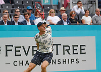 Tennis - 2019 Queen's Club Fever-Tree Championships - Day Three, Wednesday<br /> <br /> Men's Singles, First Round: Juan Martin Del Potro (ARG) Vs. Denis Shapovalov (CAN)<br /> <br /> Denis Shapovalov (CAN) gets his Tennis arm wrapped behind his back after striking the ball on Centre Court.<br />  <br /> COLORSPORT/DANIEL BEARHAM