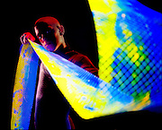 Young man with colorful glowing mesh.Black light