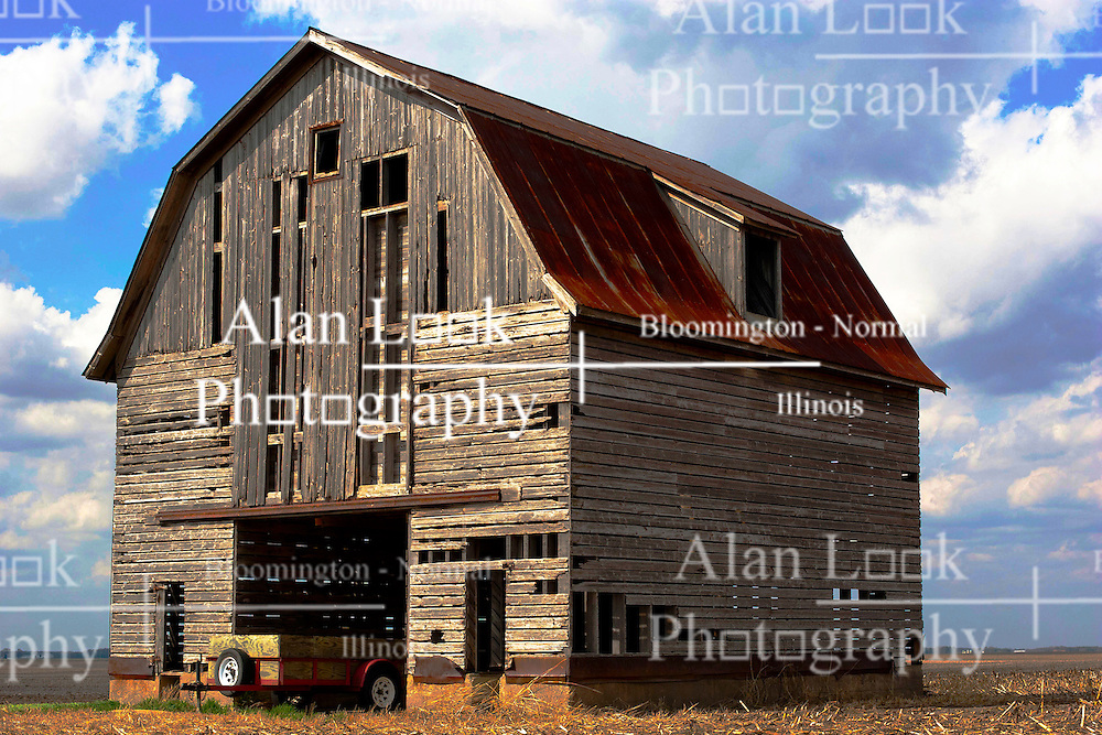 2012, March 18:  A farm building, Barn or crib sits idle in the barn lot in disrepair with a newer wagon filled with straw bales.