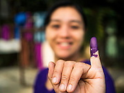 08 NOVEMBER 2015 - YANGON, MYANMAR:  A woman displays her pinkie finger, stained with ink, a sign that she voted in North Okkalapa, a township outside of Yangon center Sunday. The citizens of Myanmar went to the polls Sunday to vote in the most democratic elections since 1990. The National League for Democracy, (NLD) the party of Aung San Suu Kyi is widely expected to get the most votes in the election, but it is not certain if they will get enough votes to secure an outright victory. The polls opened at 6AM. In Yangon, some voters started lining up at 4AM and lines were reported to long in many polling stations in Myanmar's largest city.     PHOTO BY JACK KURTZ