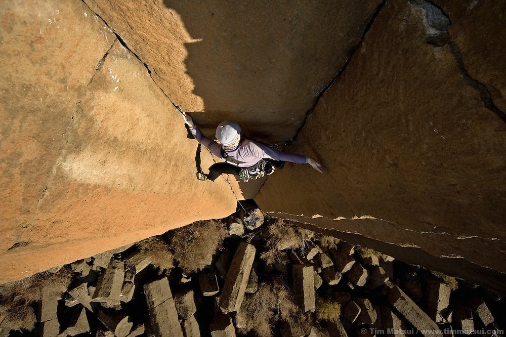 A caucasian woman climbing basalt cracks in Oregon...