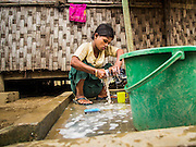 07 NOVEMBER 2014 - SITTWE, RAKHINE, MYANMAR: A Rohingya Muslim woman does her laundry in an IDP camp near Sittwe. After sectarian violence devastated Rohingya communities and left hundreds of Rohingya dead in 2012, the government of Myanmar forced more than 140,000 Rohingya Muslims who used to live in and around Sittwe, Myanmar, into squalid Internal Displaced Persons camps. The government says the Rohingya are not Burmese citizens, that they are illegal immigrants from Bangladesh. The Bangladesh government says the Rohingya are Burmese and the Rohingya insist that they have lived in Burma for generations. The camps are about 20 minutes from Sittwe but the Rohingya who live in the camps are not allowed to leave without government permission. They are not allowed to work outside the camps, they are not allowed to go to Sittwe to use the hospital, go to school or do business. The camps have no electricity. Water is delivered through community wells. There are small schools funded by NOGs in the camps and a few private clinics but medical care is costly and not reliable.   PHOTO BY JACK KURTZ