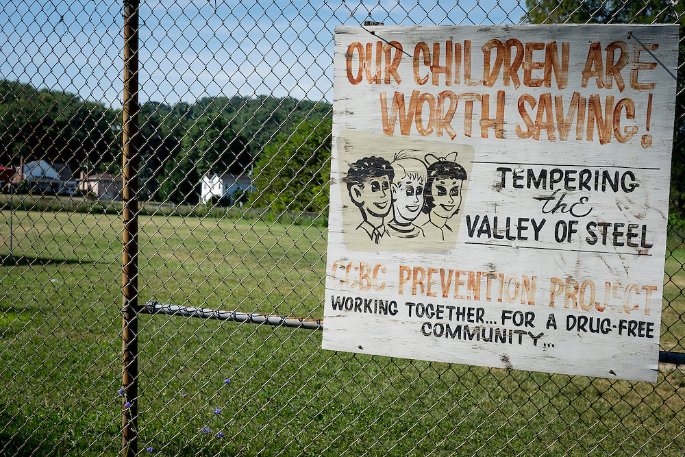 A sign advertising for a drug free community project is attached to the fence at the Lefty Cepull Field, located in Plan 12 in Aliquippa. Plan 12 is one of the neighborhoods in Aliquippa with serious drug problems.