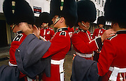 While on ceremonial duties at the Queen's Buckingham Palace, members of the Welsh Guards prepare the finer details of uniform presentation at the Wellington barracks, opposite the Palace in central London, England. Buffing up their bearskin hats and brushing away any specks of dust from shoulders, they each help the other appear as near-perfect as they can before parading in front of thousands during the Changing of the Guard or at other times, during tropping of the Colour on the Queen's birthday occasion. Formed in 1915 by order of King George V,  have fought in every war since but are housed at the Wellington Barracks purely for ceremonial reasons, also serving on active duty in the world's trouble spots, where their professionalism is demanded by their British Ministry of Defence masters.